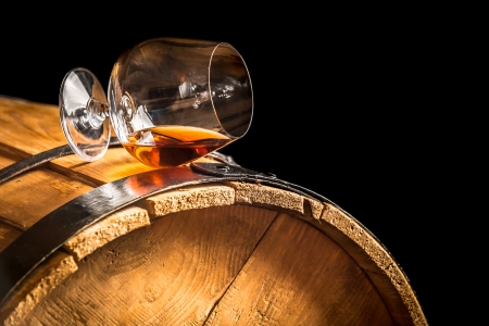 Glass of cognac on the vintage barrel photo