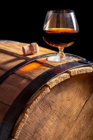 Glas cognac op de vintage houten vat Stockfoto