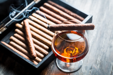 Burning cigar on humidor and cognac in glass photo