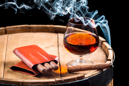 Cognac in a glass on barrel and burning cigar photo