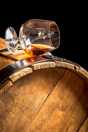 Cognac in glass on old vintage barrel photo