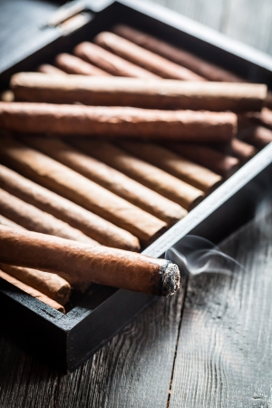 Smoke rising from a burning cigar on wooden humidor photo