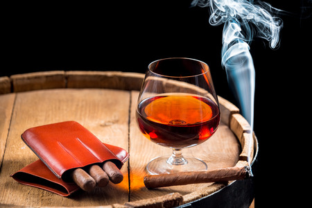 Cognac in a glass on wooden barrel photo