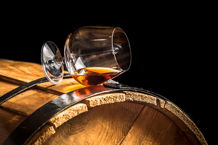 Glass of cognac on the old wooden barrel