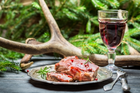 Red wine in a glass and venison on a plate Stock Photo