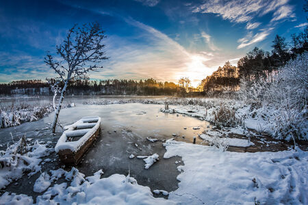 Sunrise on winter lake covered with snow photo