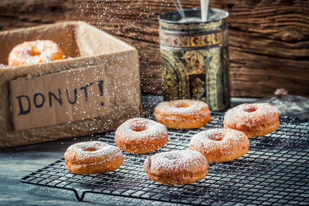 Icing sugar falling on fresh donuts photo