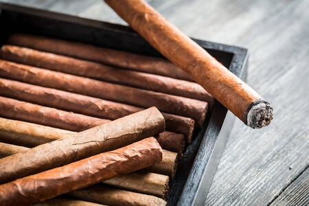 Burning cigar with smoke on wooden humidor photo