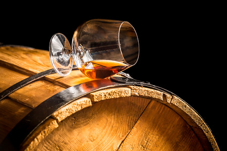brandy: Glass of cognac on the vintage barrel
