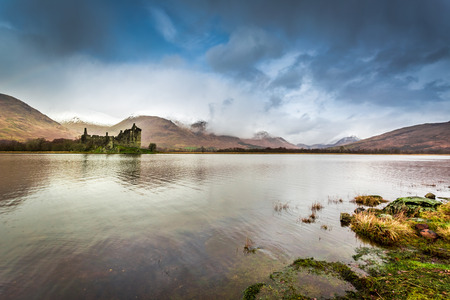 typically scottish: Ruins of old castle in Scotland over the lake Stock Photo