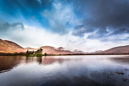 typically scottish: Ruins of the castle on the lake in winter