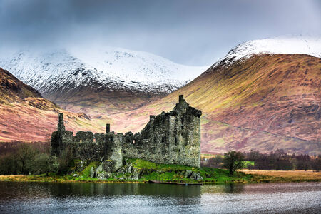 typically scottish: Old ruined castle on the background of snowy mountains