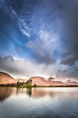 typically scottish: Ruins of the castle on the lake Editorial