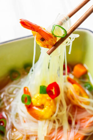 Closeup of soup with noodles and spicy shrimp photo
