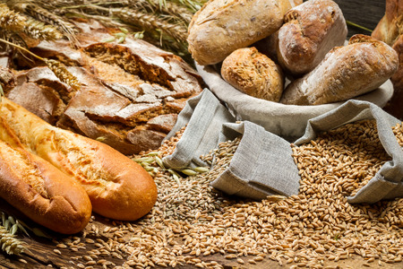 Various kinds of whole wheat bread on old wooden table photo