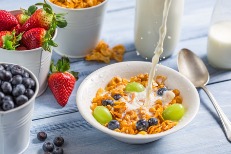 Cornflakes with fruits flooded with milk photo