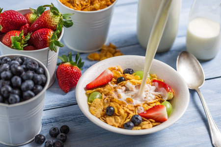 preservatives: Pouring milk into cornflakes with fruits Stock Photo
