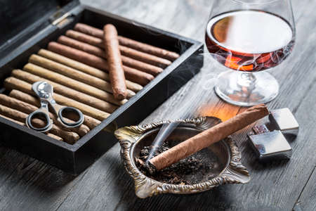 Burning cigar in ashtray and cognac photo