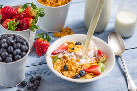 Pouring milk into cornflakes with fruits photo