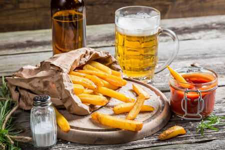 Closeup of homemade fresh fries with cold beer photo