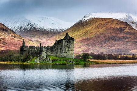 highlands region: Old ruined castle on the background of snowy mountains