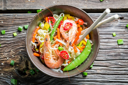 Closeup of chinese noodles, vegetables and prawns photo