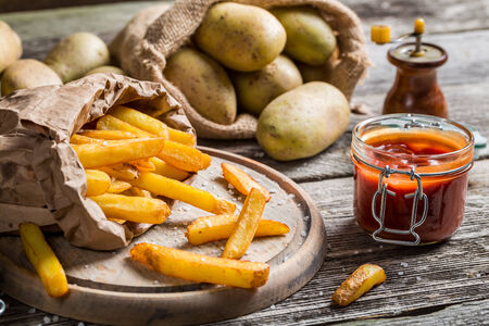 Closeup of homemade fries with ketchup and salt photo