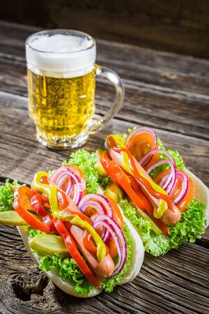 Fresh hot dog with sausage and vegetables and beer photo
