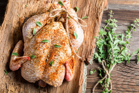 Raw chicken with herbs ready to roast photo