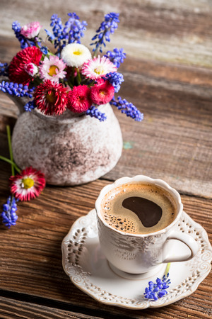 Coffee and spring flowers on old wooden table photo