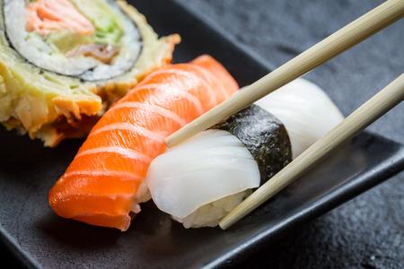 Färsk sushi äts med pinnar Stockfoto