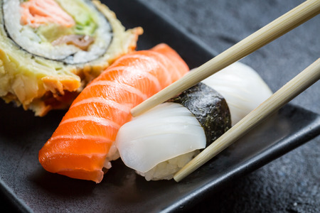 Fresh sushi eaten with chopsticks Stock Photo