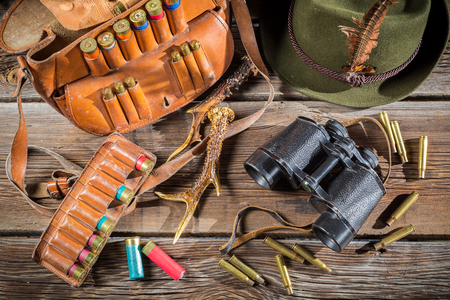 Bag with bullets, binoculars and hat in a hunting lodge photo