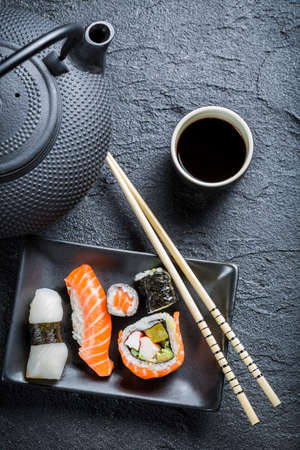 Fresh sushi served in a black ceramic photo