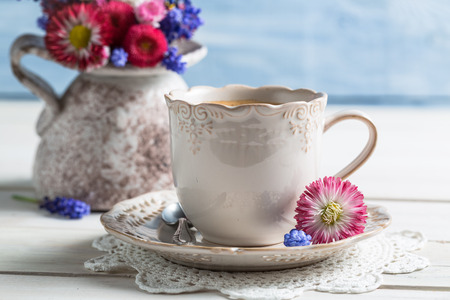 Spring flowers and coffee on old table photo