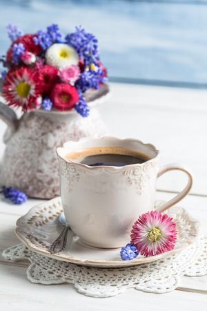 Cup of coffee and daisy flowers photo