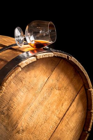 Glas cognac op de oude houten vat Stockfoto