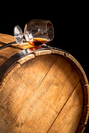 Glass of cognac on the old wooden barrel Reklamní fotografie - 28682642