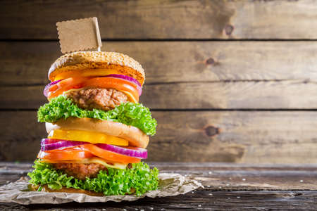Double-decker burger on wooden background with space to menu photo