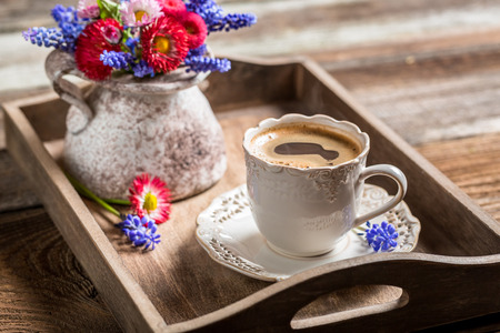 Coffee and spring flowers on wooden tray photo
