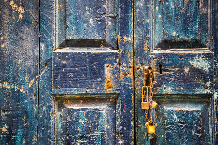 Old wooden blue door with padlocks photo