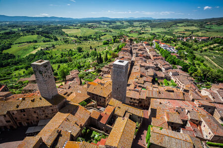View of the red roofs and green valley in San Gimignano, Italy photo