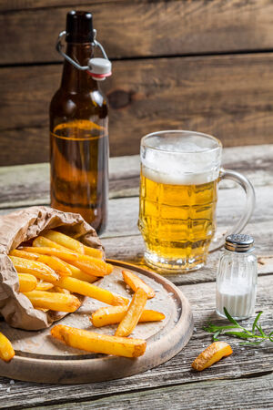 Fresh french fries served with beer photo