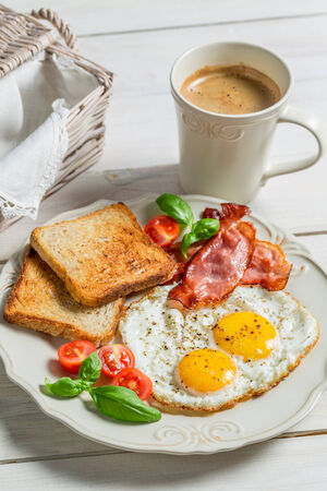 Eggs, bacon, toast and coffee for breakfast photo