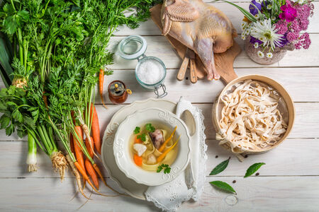 Homemade chicken noodle soup with ingredients photo