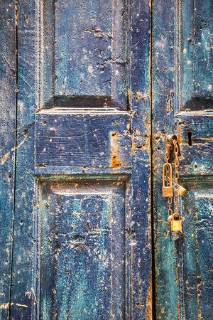 Old wooden blue door with padlocks photo