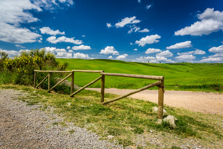 san quirico d'orcia: Old wooden fence, dirt road and green field Stock Photo