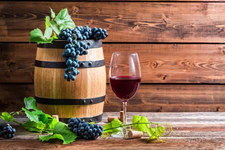 red oil lamp: Glass of red wine in a wooden cellar Stock Photo