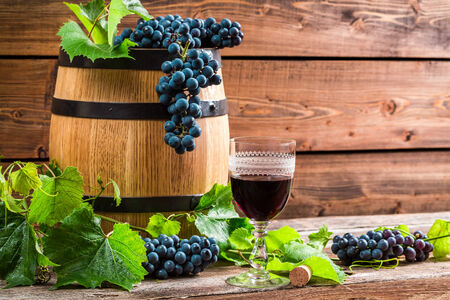 red oil lamp: Red wine in a glass and grapes Stock Photo