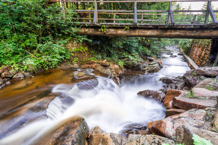 Mountain stream and an old wooden bridge photo